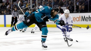 San Jose Sharks' Joe Thornton, left, shoots as Toronto Maple Leafs' Patrick Marleau (12) defends during the second period of an NHL hockey game Monday, Oct. 30, 2017, in San Jose, Calif. (AP Photo/Marcio Jose Sanchez)