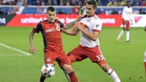 Toronto FC forward Sebastian Giovinco, left, holds off New York Red Bulls midfielder Aaron Long (33) during the second half of an MLS Eastern Conference semifinal soccer match Monday, Oct. 30, 2017, in Harrison, N.J. Toronto FC won 2-1. Faced with a New York pushback in the second half, league-leading Toronto FC served a reminder at Red Bull Arena that it can defend as well as it can attack. THE CANADIAN PRESS/AP-Bill Kostroun