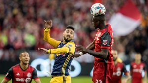 New York Red Bulls midfielder Gonzalo Veron (30) looks on as Toronto FC defender Chris Mavinga (23) heads the ball during first half MLS soccer action in Toronto on Sunday, November 5, 2017. THE CANADIAN PRESS/Mark Blinch