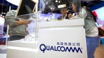 In this Thursday, April 27, 2017, file photo, visitors look at a display booth for Qualcomm at the Global Mobile Internet Conference (GMIC) in Beijing. (AP Photo/Mark Schiefelbein, File)
