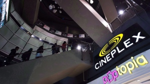 People make their way an escalator at the Cineplex Entertainment company's annual general meeting in Toronto on May 17, 2017. THE CANADIAN PRESS/Nathan Denette