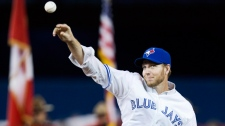 Retired pitcher and former Toronto Blue Jays ace Roy Halladay throws out the opening pitch before the Blue Jays take on the New York Yankees during first inning home opener AL baseball action in Toronto on Friday, April 4, 2014. THE CANADIAN PRESS/Peter Power