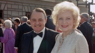 This Sept. 22, 1985, file photo shows John Hillerman, left, and Betty White, right, arriving at Emmy Awards in Pasadena, Calif. A spokeswoman for the family of Hillerman says the co-star of TV's 'Magnum, P.I.' has died. Hillerman was 84. Spokeswoman Lori De Waal said Hillerman died Thursday at his home in Houston. She said the cause of death has yet to be determined. (AP Photo/LIU, File)