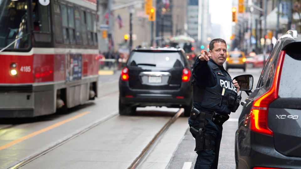 A police constable speaks to a driver during the second day of the King Street Transit Pilot involving city streetcars on Monday, November 13, 2017. THE CANADIAN PRESS/Doug Ives