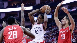 Toronto Raptors guard DeMar DeRozan (10) drives up a shot between Houston Rockets forward Tarik Black (28) and forward Ryan Anderson (33) during the first half of an NBA basketball game, Tuesday, Nov. 14, 2017, in Houston. (AP Photo/Michael Wyke)