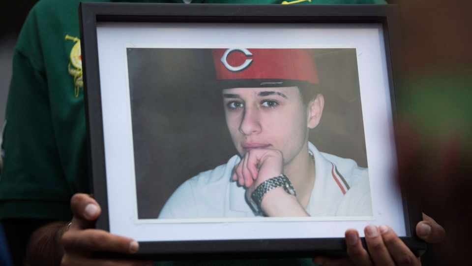 A photo of Sammy Yatim is held by one of the teen's friends at a Toronto courthouse after the sentencing of Const. James Forcillo in Toronto on Thursday, July 28, 2016. THE CANADIAN PRESS/Michelle Siu