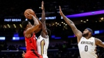Toronto Raptors guard DeMar DeRozan (10) shoots over New Orleans Pelicans guard Jrue Holiday (11) and center DeMarcus Cousins (0) in the first half of an NBA basketball game in New Orleans, Wednesday, Nov. 15, 2017. (AP Photo/Scott Threlkeld)