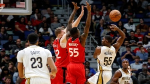 New Orleans Pelicans guard E'Twaun Moore (55) passes to forward Anthony Davis (23) as Toronto Raptors center Jakob Poeltl (42) and guard Delon Wright (55) try to block him in the first half of an NBA basketball game in New Orleans, Wednesday, Nov. 15, 2017. (AP Photo/Scott Threlkeld)