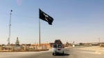 This Tuesday, July 22, 2014 file photo shows a motorist passing by a flag of the Islamic State group in central Rawah, 175 miles (281 kilometers) northwest of Baghdad, Iraq. Iraq's Defense Ministry said Friday, Nov. 17, 2017 Iraqi forces have retaken the last IS-held town in the country, more than three years after the militant group stormed nearly a third of Iraqi territory.(AP Photo, File)
