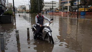A man with a motorcycle drives along a flooded street in Petralona district of Athens on Friday , Nov. 17, 2017. Greece's fire department says two more people have been reported missing after deadly flash flooding west of Athens that is confirmed to have killed at least 16 people.(AP Photo/Petros Giannakouris)