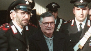 In this Jan. 16, 1996 file photo, Mafia ''boss of bosses'' Salvatore ''Toto'' Riina, center, enters handcuffed into Bologna's bunker-courtroom, escorted by Carabinieri, Italian paramiliary police, in Bologna, Italy. Italian media is reporting that Riina has died while serving multiple life sentences. He was 87. The justice ministry on Thursday, Nov. 16, 2017, had allowed his family a bedside visit at a hospital Parma shortly before his death. He had been placed in a medically induced coma after his health deteriorated following two recent surgeries. (AP Photo/Gianni Schicchi, File)