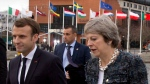 British Prime Minister Theresa May, right, speaks with French President Emmanuel Macron, left, as they walk on a pier at an EU summit in Goteborg, Sweden on Friday, Nov. 17, 2017. European Union leaders warned Britain Friday that it must do much more to convince them that Brexit talks should be broadened to future relations and trade from December. (AP Photo/Virginia Mayo)