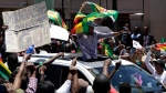 People gather to demonstrate for the ouster of 93-year-old President Robert Mugabe, outside the Zimbabwe Consulate in Johannesburg, South Africa, Saturday, Nov. 18, 2017. The 93-year-old Mugabe, the world's oldest head of state, is said to be asking for more time amid negotiations with regional leaders that seek his exit with a veneer of dignity. (AP Photo/Themba Hadebe)