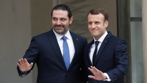 French President Emmanuel Macron, right, poses for photographers with Lebanon's Prime Minister Saad Hariri prior to their meeting at the Elysee Palace in Paris, Saturday, Nov. 18, 2017. Hariri arrived in France on Saturday from Saudi Arabia and may be back in Beirut next week, seeking to dispel fears that he had been held against his will and forced to resign by Saudi authorities.(AP Photo/Thibault Camus)