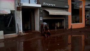 A man drops buckets with mud outside his house in Mandra western Athens, on Friday, Nov. 17, 2017. (AP Photo/Petros Giannakouris)
