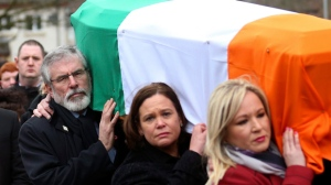 In this Thursday, March 23, 2017 file photo, Sinn Fein's Gerry Adams, left, Mary Lou McDonald, centre, and Michelle O'Neill carry the coffin of former IRA commander and Sinn Fein deputy leader Martin McGuinness to St Columba's Church in Londonderry, Northern Ireland. Gerry Adams has announced that he plans to step down as leader of Sinn Fein next year after heading the party for over 30 years. Adams said in a speech at the party's annual conference in Dublin on Saturday, Nov. 18, 2017 that he will not stand for the next Irish parliamentary election. (AP Photo/Peter Morrison, file)