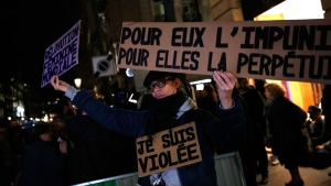 "A Tuesday, Nov. 14, 2017 file photo of an activist holding a banner reading: ""For him impunity, for her a life sentence"" during a protest in Paris. (AP Photo/Christophe Ena, File)"