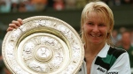 FILE - In this July 4, 1998 file photo, Jana Novotna, of the Czech Republic, displays the women's singles trophy after her victory over France's Nathalie Tauziat in the final on Wimbledon's Centre Court. The WTA says the 1998 Wimbledon champion Jana Novotna of the Czech Republic has died. In a Monday, Nov. 20, 2017 statement, the WTA say Novotna died after battling a cancer on Sunday, Nov. 19. She was 49. (AP Photo/Dave Caulkin, File )