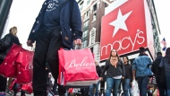 FILE - In this Nov. 27, 2015, file photo, shoppers carry bags as they cross a pedestrian walkway near Macy's in Herald Square, in New York. At Macy's flagship store in New York, a chance to sit on Santa Claus' lap is by appointment only in 2017, for the first time ever. (AP Photo/Bebeto Matthews, File)