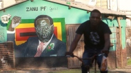 A man cycles past the Zanu pf offices bearing a painting of Zimbabwean President Robert Mugabe in Mbare, Harare, Monday, Nov, 20, 2017.  (AP Photo/Tsvangirayi Mukwazhi)