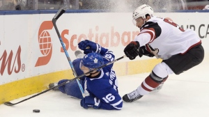 Toronto Maple Leafs centre Mitchell Marner (16) loses his edge and falls in the corner as Arizona Coyotes defenceman Jason Demers (55) defends during first period NHL hockey action in Toronto on Monday, November 20, 2017. THE CANADIAN PRESS/Nathan Denette