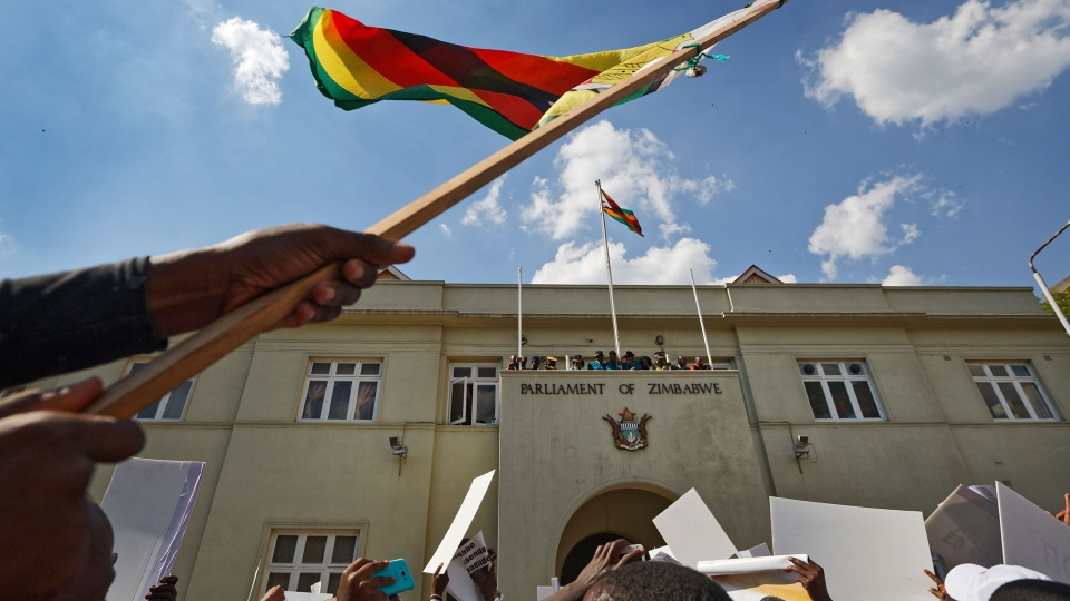 Protesters calling for the impeachment of President Robert Mugabe brandish a national flag as they demonstrate outside the parliament building in downtown Harare, Zimbabwe Tuesday, Nov. 21, 2017. (AP Photo/Ben Curtis)