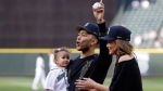 Entertainer John Legend, center, waves and cheers as he walks off the field with his wife Chrissy Teigen and their daughter Luna Stephens after the family threw out the ceremonial first pitch before a baseball game between the Seattle Mariners and the Minnesota Twins, Tuesday, June 6, 2017, in Seattle. (AP Photo/Elaine Thompson)
