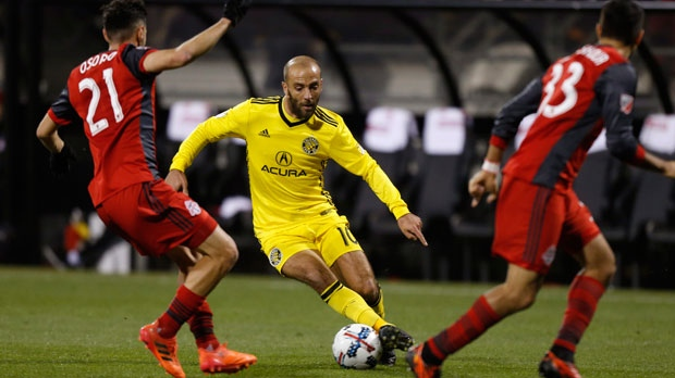 Columbus Crew's Federico Higuain, center, dribbles the ball between Toronto FC's Jonathan Osorio, left, and Steven Beitashour during the first half of an MLS Eastern Conference championship soccer match Tuesday, Nov. 21, 2017, in Columbus, Ohio. (AP Photo/Jay LaPrete)