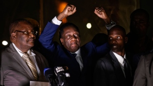 Zimbabwe's President in waiting Emmerson Mnangagwa, center, greets supporters gathered outside the Zanu-PF party headquarters in Harare, Zimbabwe Wednesday, Nov. 22, 2017. (AP Photo/Ben Curtis)