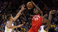 Toronto Raptors' Delon Wright (55) shoots between Golden State Warriors' Stephen Curry, left, and Jordan Bell (2) during the first half of an NBA basketball game Wednesday, Oct. 25, 2017, in Oakland, Calif. (AP Photo/Ben Margot)