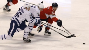 Florida Panthers' Jonathan Huberdeau , right, reaches for the puck as Toronto Maple Leafs' Zach Hyman, center, and Toronto Maple Leafs' Mitchell Marner (16) defend during the second period of an NHL hockey game, Wednesday, Nov. 22, 2017, in Sunrise, Fla. (AP Photo/Luis M. Alvarez)
