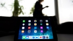 A woman uses her smart phone as apps are shown on an iPad in Mississauga, Ont., on Monday, November 13, 2017. THE CANADIAN PRESS/Nathan Denette