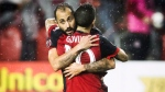 Toronto FC's Victor Vazquez and Sebastian Giovinco embrace after defeating the New York Red Bulls on away goals to win the MLS Eastern Conference semifinal in Toronto on Sunday, November 5, 2017. THE CANADIAN PRESS/Mark Blinch