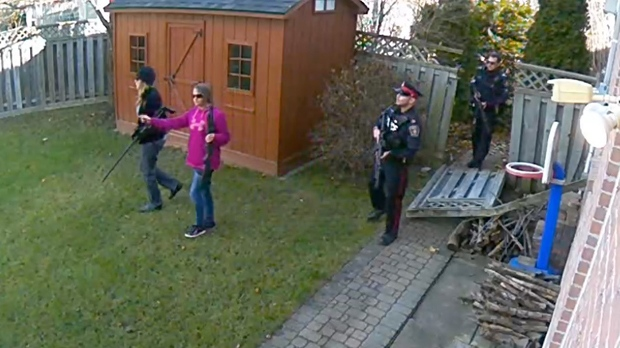 Armed MNR officials and police follow the path of a moose through a backyard in Markham. (Provided)