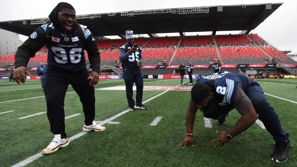 Toronto Argonauts defensive lineman Jeff Luc, left, and defensive lineman Sadat Sulleyman watch offensive lineman William Campbell, right, play around during practice for the Grey Cup in Ottawa on Saturday, November 25, 2017. THE CANADIAN PRESS/Sean Kilpatrick