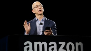 In this Wednesday, June 18, 2014, file photo, Amazon CEO Jeff Bezos demonstrates the new Amazon Fire Phone, in Seattle.  (AP Photo/Ted S. Warren, File)