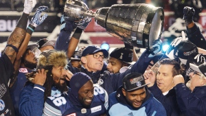 Toronto Argonauts head coach Marc Trestman, centre, and players celebrate with the Grey Cup after defeating the Calgary Stampeders in CFL football action in the 105th Grey Cup on Sunday, November 26, 2017 in Ottawa. THE CANADIAN PRESS/Ryan Remiorz