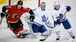 Toronto Maple Leafs goalie Frederik Andersen, centre, from Denmark, and teammate Nikita Zaitsev, right, from Russia, look on as Calgary Flames' Matthew Tkachuk trips over Andersen's pads during third period NHL hockey action in Calgary, Tuesday, Nov. 28, 2017.THE CANADIAN PRESS/Jeff McIntosh