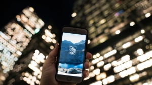 A mobile bank app splash screen is shown against a backdrop of lights from bank headquarters in Toronto's Financial District Thursday, Nov.29, 2017. THE CANADIAN PRESS/Graeme Roy