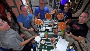 In this Nov. 18, 2017 photo provided by NASA, from left, American Mark Vande Hei, Russian Sergei Ryazanskiy, Italian Paolo Nespoli, American Joe Acaba and American Randy Bresnik display the results of their made-from-scratch pizza pies at the International Space Station. The fixings flew up in November on a commercial supply ship. (NASA via AP)