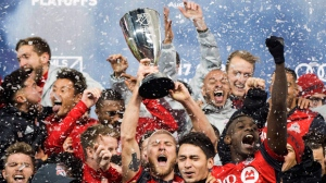 Toronto FC midfielder Michael Bradley, center, hoists the Eastern Conference championship trophy after defeating the Columbus Crew to advance to the MLS Championship finals, Wednesday, Nov. 29, 2017 in Toronto. (Nathan Denette/The Canadian Press via AP)