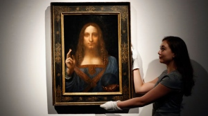 "In this Oct. 24, 2017 file photo, an employee poses with Leonardo da Vinci's ""Salvator Mundi"" on display at Christie's auction rooms in London. (AP Photo/Kirsty Wigglesworth, File)"
