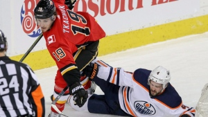 Calgary Flames' Matthew Tkachuk takes down Edmonton Oilers' Kris Russell during first period NHL hockey action in Calgary, Saturday, Dec. 2, 2017.THE CANADIAN PRESS/Mike Drew