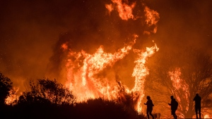 Motorists on Highway 101 watch flames from the Thomas fire leap above the roadway north of Ventura, Calif., on Wednesday, Dec. 6, 2017. (AP Photo/Noah Berger)