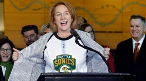Seattle Mayor Jenny Durkan pulls back her jacket to reveal a Seattle SuperSonics T-shirt as she speaks before signing an agreement to renovate KeyArena, Wednesday, Dec. 6, 2017, in Seattle. THE CANADIAN PRESS/AP-Elaine Thompson