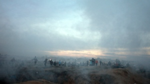 Teargas enshrouds Palestinian protesters as they run for cover, the teargas fired by Israeli troops during clashes on the Israeli border with Gaza, Sunday, Dec. 10, 2017. (AP Photo/ Khalil Hamra)