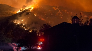In this Sunday, Dec. 10, 2017, photo flames from a wildfire consume the mountainside near the Cate School campus in Carpinteria, Calif. (Kenneth Song/Santa Barbara News-Press via AP)