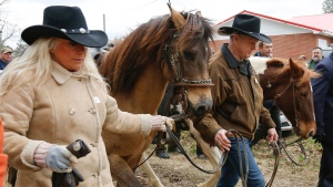 U.S. Senate candidate Roy Moore, and his wife, Kayla Moore, walk their horses after they voted Tuesday, Dec. 12, 2017, in Gallant, Ala. (AP Photo/Brynn Anderson)