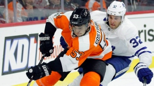 Philadelphia Flyers' Shayne Gostisbehere, left, and Toronto Maple Leafs' Josh Leivo chase the puck behind Flyers' goal during the first period of an NHL hockey game, Tuesday, Dec. 12, 20017, in Philadelphia. (AP Photo/Tom Mihalek)