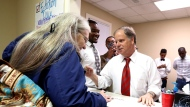 FILE - In this Nov. 29, 2017, file photo, Doug Jones, right, checks in volunteer, Chyrl Willis, left, as he stops along the campaign trail in Montgomery, Ala. (AP Photo/Brynn Anderson, File)